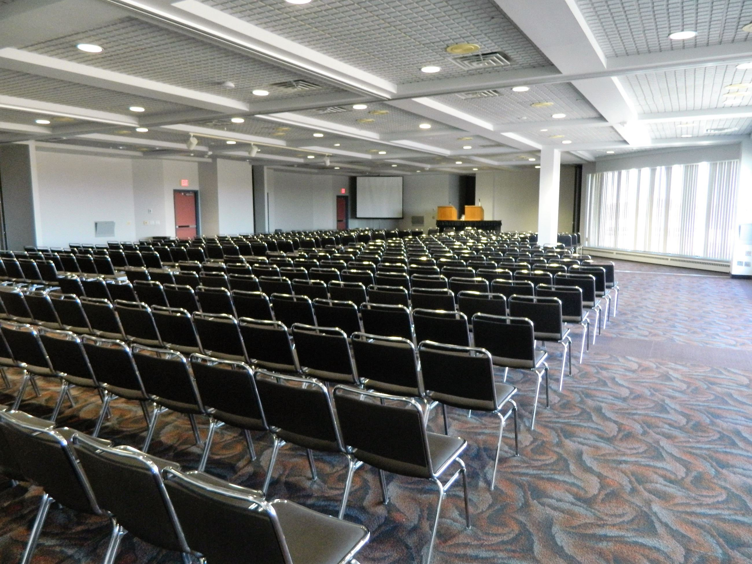 Room set up with chairs facing a projector screen and podium, accommodating 370 people