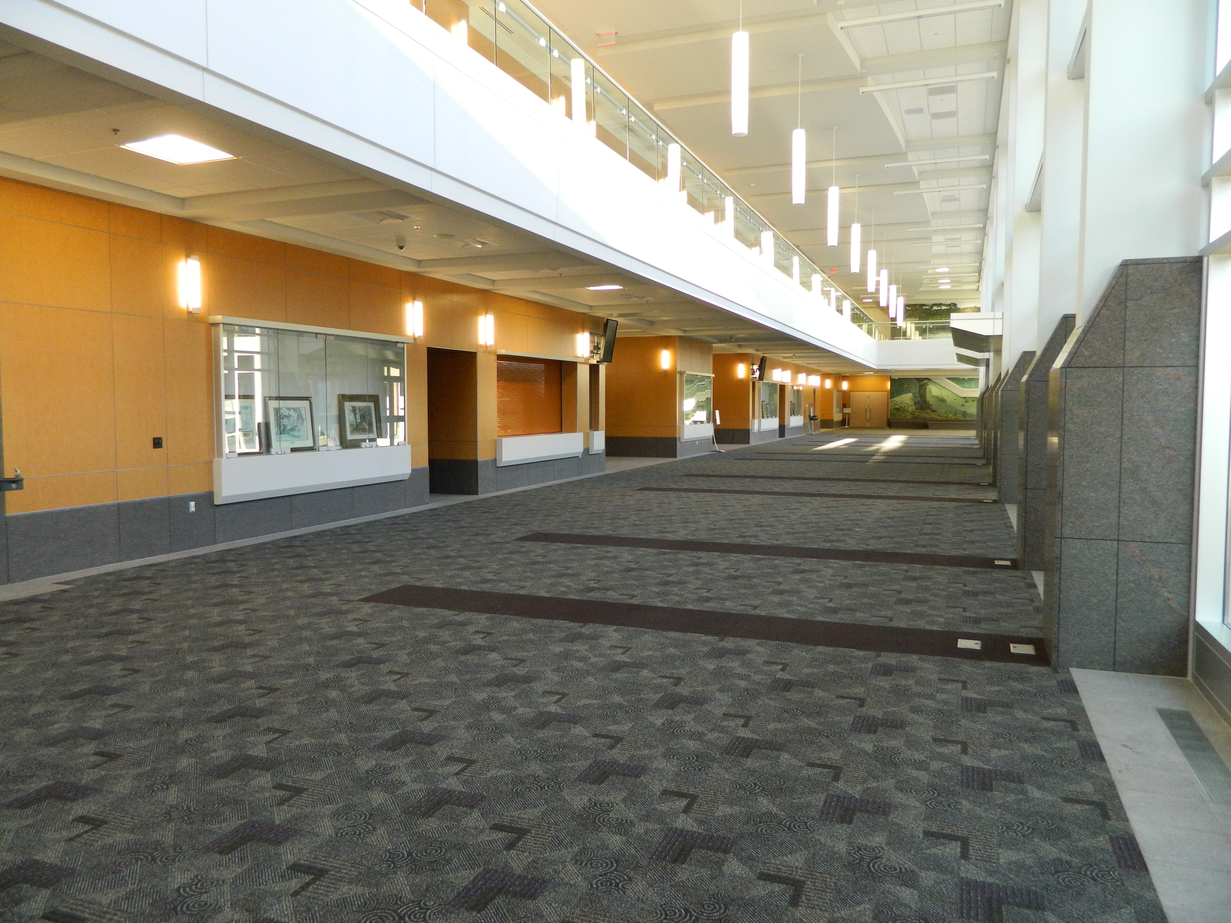 Main hall of Convention Center with wall displays, carpeted floor, and high ceilings